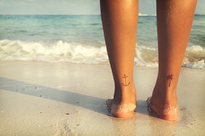 Leisure in summer - Rear of beautiful women tan relax on beach with tattoo on foot.